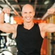 Smiling man standing and showing his muscles — Stock Photo #65057129