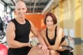 Ritratto di coppia sportiva con manubri sorridendo alla telecamera — Foto Stock