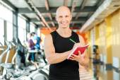 Fitness instructor writing notes in notebook — Foto de Stock