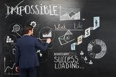 Businessman painting symbols on chalkboard — ストック写真