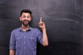 Cheerful casual man pointing on blank chalkboard — Stockfoto
