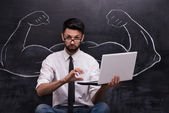 Businessman with laptop and painted muscular arms on chalkboard — Stock Photo