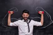 Businessman with dumbbells and painted muscular arms on chalkboard — Stockfoto