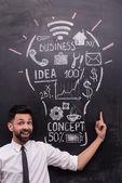 黒板に描かれた電球を指してビジネスマンを笑顔 — ストック写真