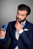 Stylish man with beard using electric shaver — Stock Photo