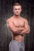 Young well formed man looking at camera with arms folded — Stock Photo