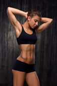 Mixed race sporty woman demonstrating biceps and slim figure — Stock Photo