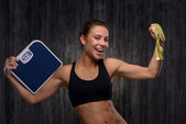 Smiling mixed race sporty woman holding weighs and measuring tape — Stock Photo