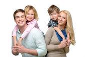 Smiling children riding piggyback on parents — Stock Photo