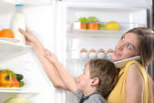 Mother with phone helping son to get milk from fridge — Stock Photo
