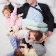 Top view of chidren sleeping all over father — Stock Photo #69417559