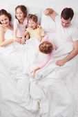 Family of five under blanket in the morning — Stock Photo