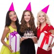 Happy three women with birthday hats and colourful presents — Stock Photo #69642351