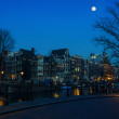 Moon over Amsterdam, Netherlands canals and bridges — Stock Photo #76933205