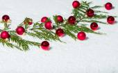 Evergreen bough with red ornaments — Stock Photo
