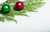 Two Christmas ornaments on cedar branch — Stock Photo