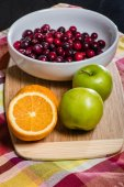 Bowl of cranberries with apples and oranges — Stock Photo
