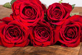 Five bright red roses on a table — Stock Photo