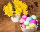 Bowl of dyed eggs with vase of flowers — Stock Photo