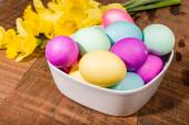 Bowl of dyed Easter eggs with daffodils — Stock Photo
