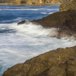 Waves breaking over dark rocks — Stock Photo #74697281