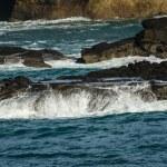 Waves breaking over dark rocks — Stock Photo #74697299