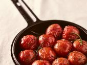Grilled cherry tomatoes and cast iron pot — Stock Photo