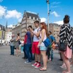 Tourists take picturesin Dam square - Amsterdam — Stock Photo #58728775