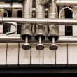 Detail of trumpet lying on the piano keys — Stock Photo #77046089