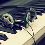 Headphones lying on the piano keys — Stock Photo #77046695