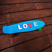 Word love on the blue penny board — 图库照片