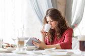 Unga leende kvinna dricker kaffe på ett kafé — Stockfoto