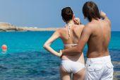 A beautiful couple standing near the sea — Stockfoto