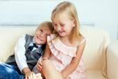 Brother and sister are sitting on the sofa — Stock Photo