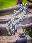 Heavy metal chains on old wooden piles — Stockfoto