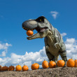 Dinosaur holding pumpkin in mouth — Stock Photo #54330213