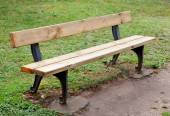 Wooden bench in the park on grass — Stock Photo