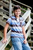 Nice preteen boy smiling in wooden stairs — Stock Photo