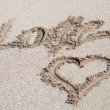 Love written on the sand with a hearth drawing — Stock Photo #56827331