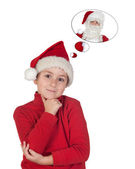 Adorable child with Christmas hat thinking in Santa Claus — Stock Photo