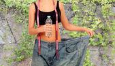 Thin woman stuck in huge pants  — Stock Photo