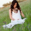 Relaxed pregnant woman sitting on the grass — Stock Photo #67854849
