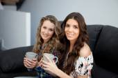 Girls holding cups with hot drink — Stock Photo