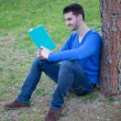 Cool man reading a book next a tree — Stock Photo #71511941
