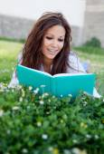 Reading a book lying on the grass — Stock Photo