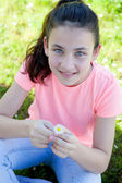 Happy casual preteen smelling a daisy — Stock Photo
