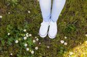 Whit white sneakers in a flowery meadow — Stock Photo