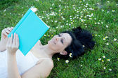 Woman lying on a flowered meadow reading a book — Stock Photo