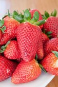 Delicious red strawberries on a white plate  — Stock Photo