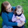 Grandmother with granddaughter sitting on grass — Stock Photo #76381053